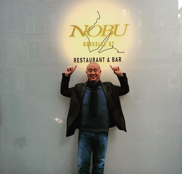 a man standing in front of a restaurant logo