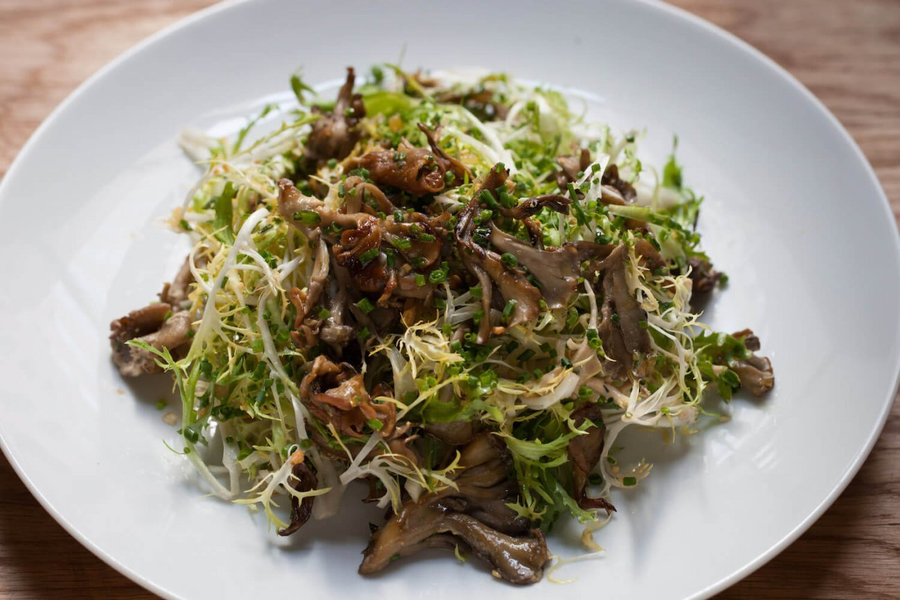 WARMED WILD MUSHROOM SALAD WITH FRISEE, ANCHOVY VINAIGRETTE, AND FRESH PARSLEY
