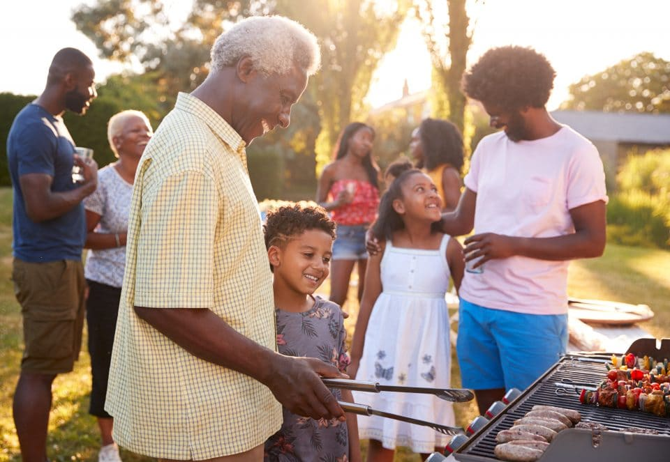 Grandad and grandson grilling at a family barbecue