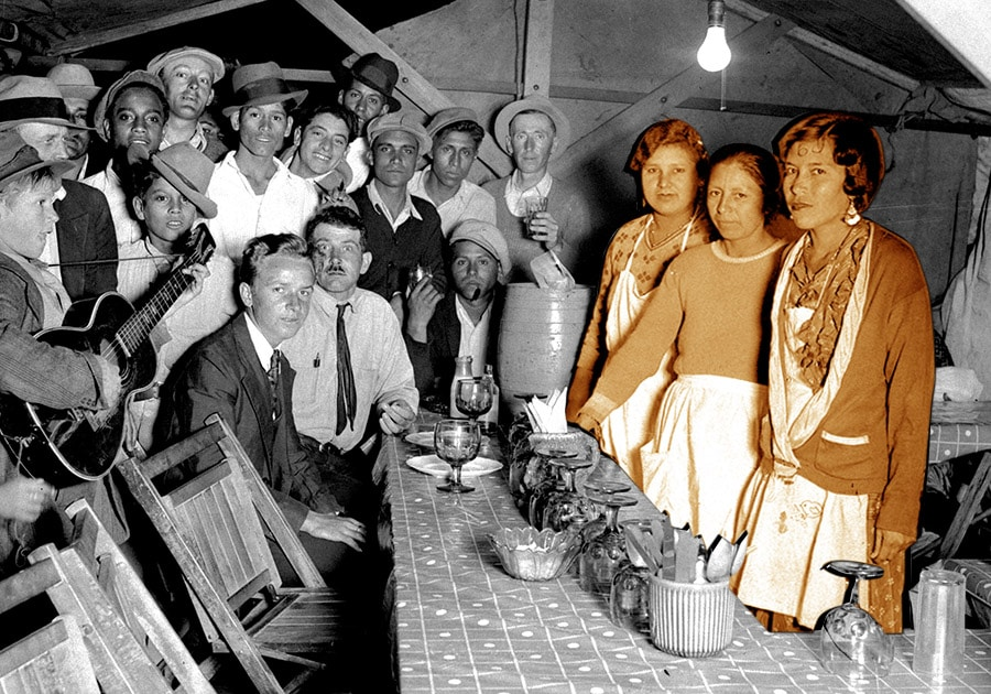 old photo of three chili queens and a group of men inside a tent, eating, drinking and smoking.