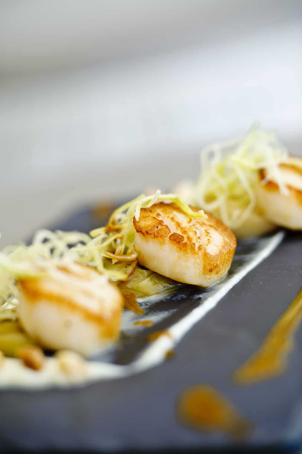 Image of Grilled Scallops, Jerusalem Artichoke, Leeks And Macadamia Praline With Apple Balsamic, Chefs Pencil