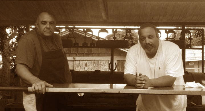 two men sitting outside on a terrace